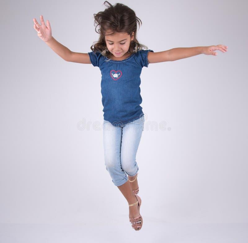 Meisje gelukkig springen en neer het kijken stock afbeelding