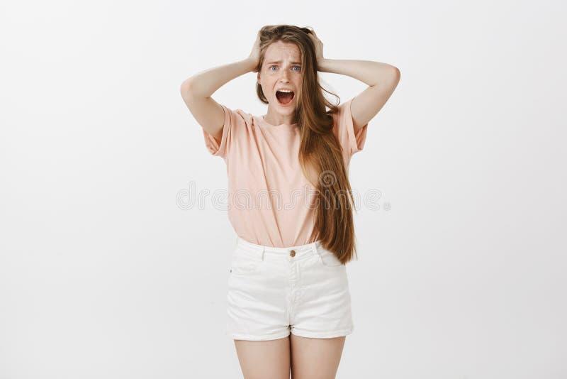 Meisje gevoel geschokte wordt geroofd Portret die van overweldigd gefrustreerd jong wijfje met leuke sproeten, handen op haar hou stock fotografie
