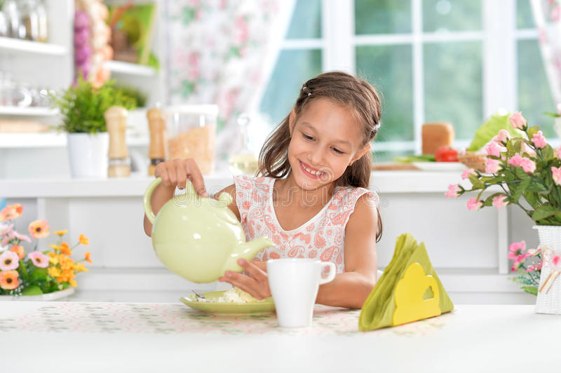 Meisje gietende thee stock foto's