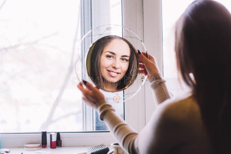 meisje glimlachen die in de spiegel kijken stock afbeelding