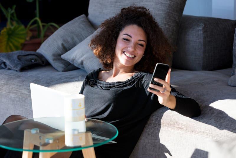 Meisje glimlachen die smartphone bekijken stock afbeelding