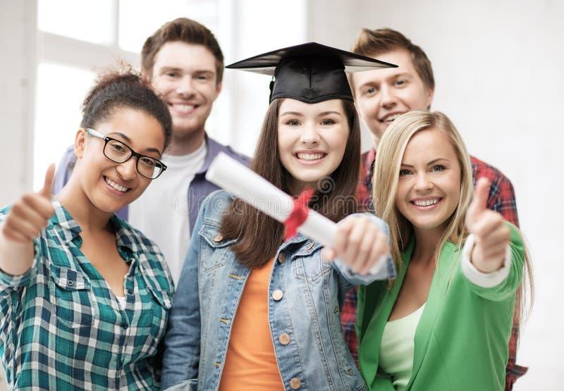Meisje in graduatie GLB met diploma en studenten royalty-vrije stock foto's