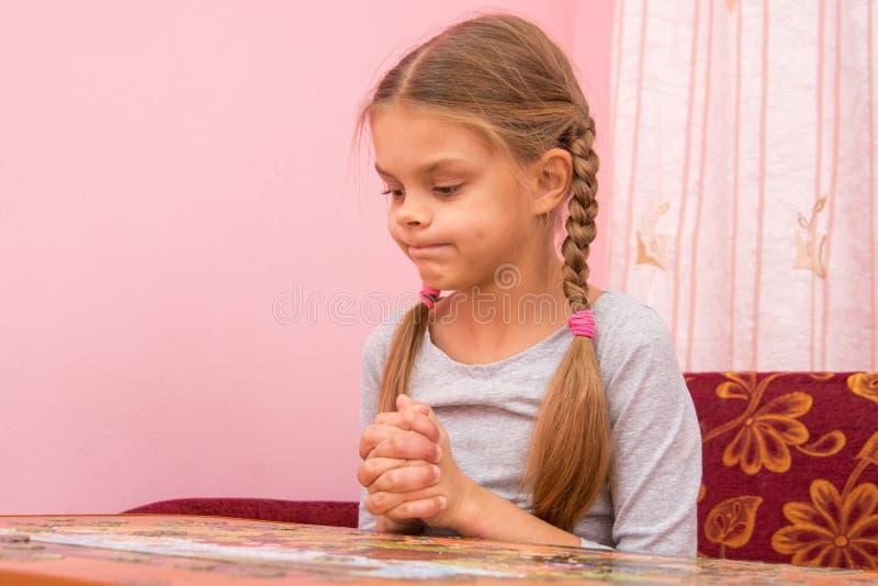 Meisje grappige gedachte het pruilen wangen die beeldraadsels verzamelen royalty-vrije stock foto's