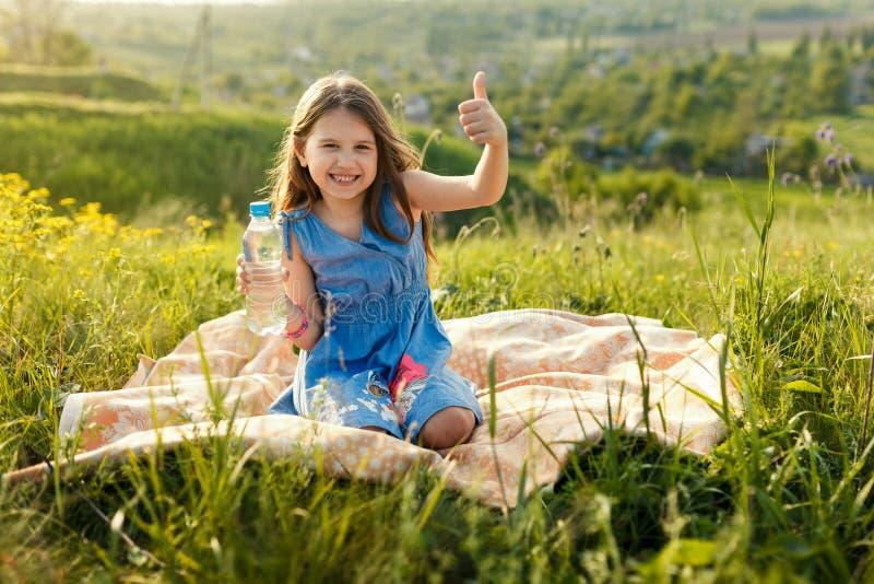 Meisje in gras met plastic waterfles royalty-vrije stock foto