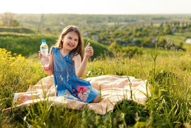 Meisje in gras met plastic waterfles stock afbeelding