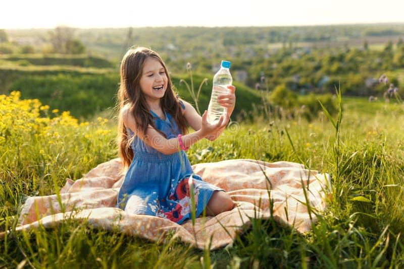 Meisje in gras met plastic waterfles stock foto's
