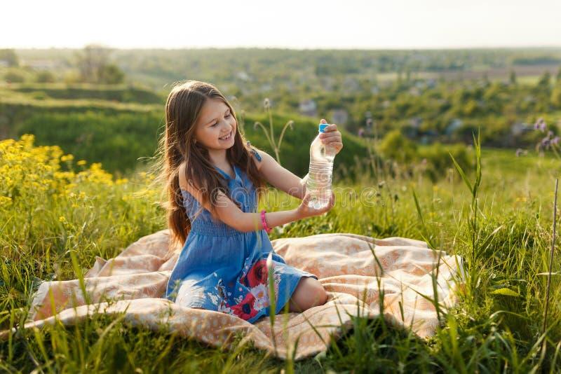 Meisje in gras met plastic waterfles stock fotografie