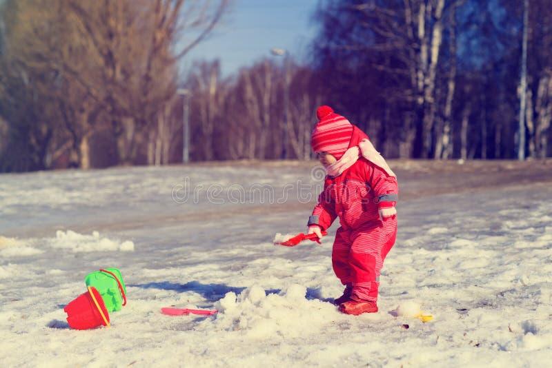 Meisje gravende sneeuw in de winter, jonge geitjesactiviteiten stock foto's