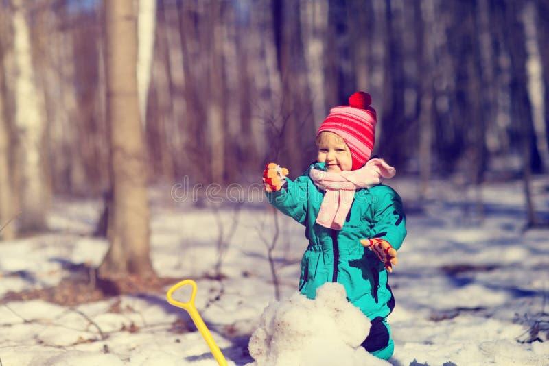 Meisje gravende sneeuw in de winter, jonge geitjesactiviteiten stock afbeeldingen