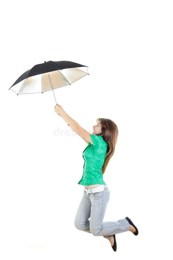 Meisje in groen overhemd en grijze jeansbroek met paraplu het springen royalty-vrije stock foto