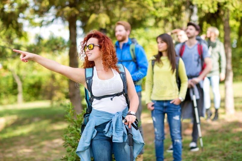 Meisje in groep wandelaars die iets richten stock afbeeldingen