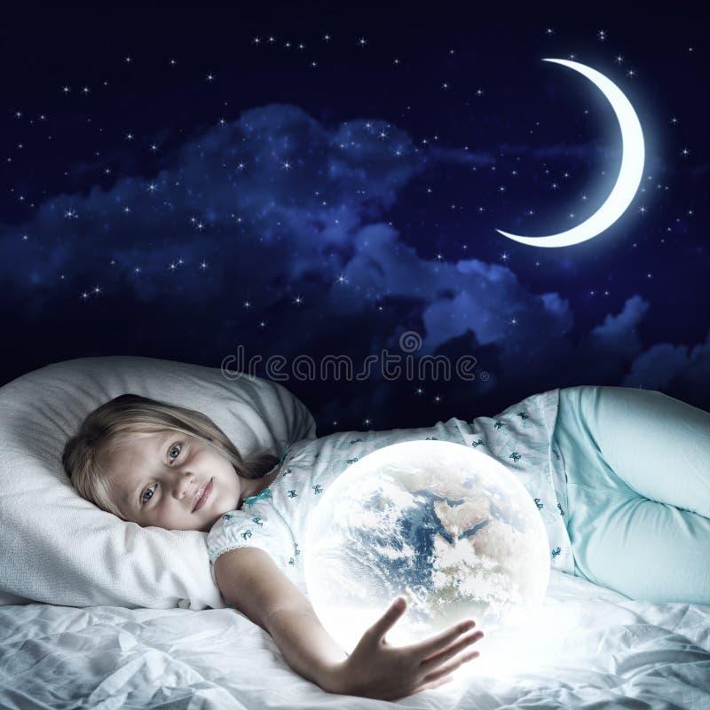 Meisje in haar bed en gloeiende bol stock foto