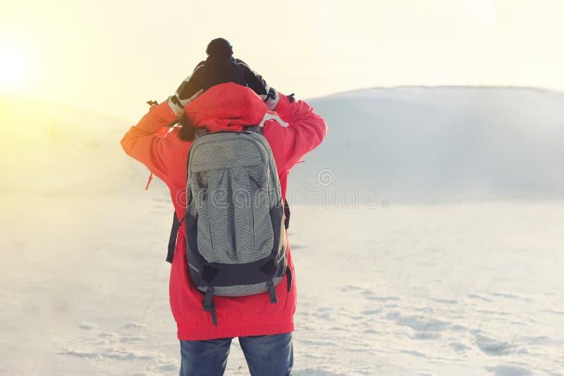 Meisje in heldere kleren die zich in een sneeuwwildernis bevinden, die zijn hoofd houden stock fotografie
