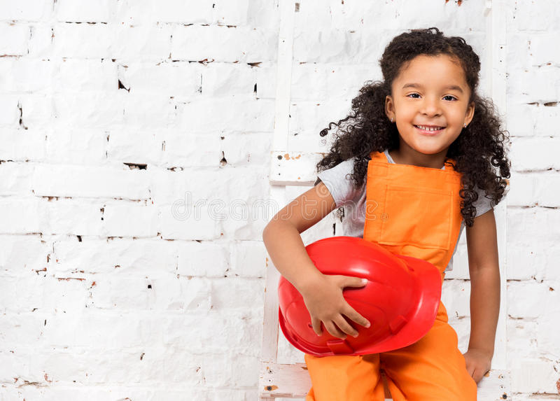 Meisje in hersteller eenvormig met helm in handen stock afbeelding