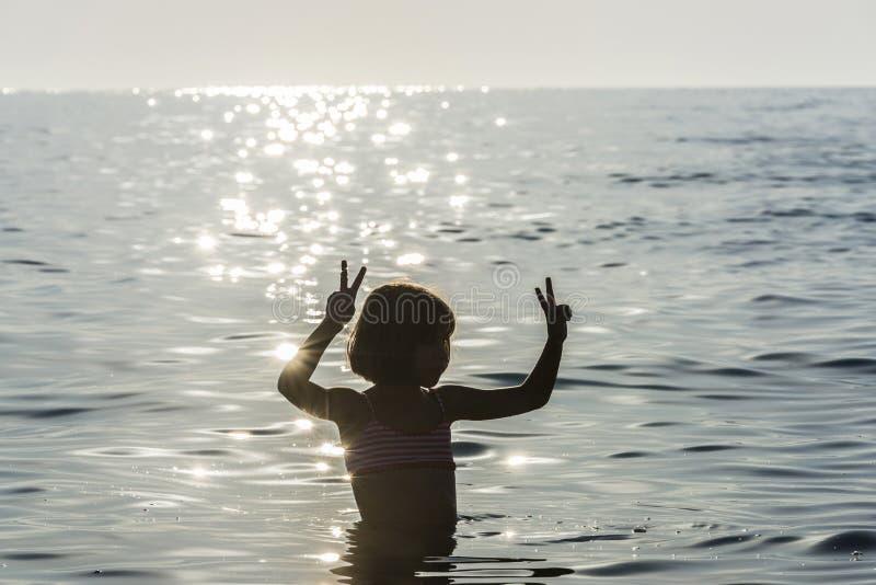 Meisje het baden in het overzees die het overwinningsteken doen stock foto