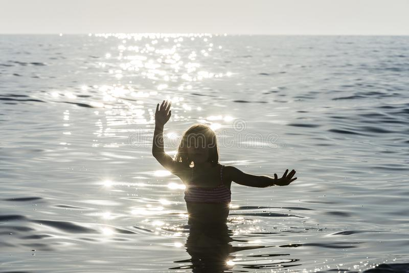 Meisje het baden in het overzees door zonnestraalbezinningen die wordt omringd stock afbeeldingen
