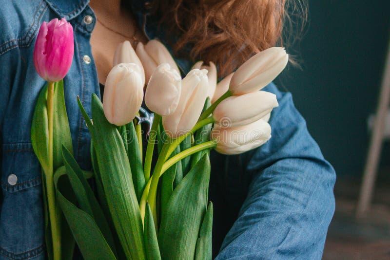 Meisje in het blauwe overhemd die achter bloementulpen verbergen in handen op houten achtergrond Een meisje in jeans houdt een bo royalty-vrije stock foto