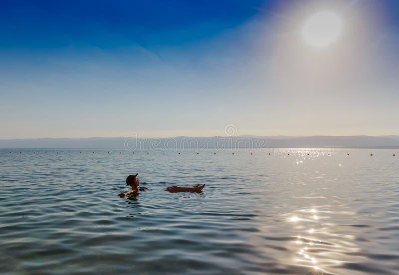 Meisje het drijven op oppervlakte van Dode Overzees, Jordanië, geniet van haar vakantie stock afbeelding
