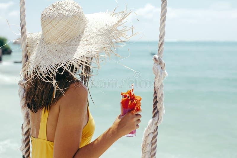 Meisje het drinken cocktail en hangig op schommeling in strandkoffie op tropisch eiland royalty-vrije stock afbeeldingen