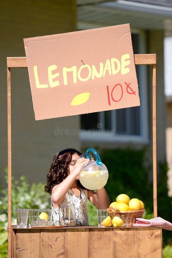 Meisje het drinken limonade van een waterkruik stock afbeeldingen