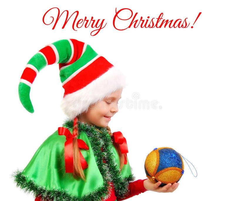 Meisje in het elf van de kostuumkerstman ` s met een Kerstmisbal stock fotografie