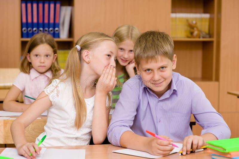Meisje het fluisteren geheimen van de jongen in het klaslokaal stock fotografie