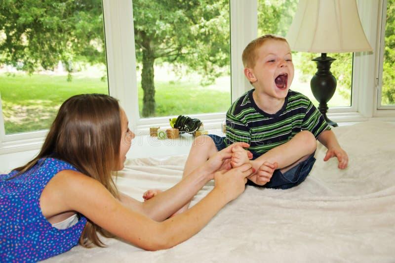 Meisje het grijpen voet, Jongen die het gekietelde lachen zijn royalty-vrije stock foto
