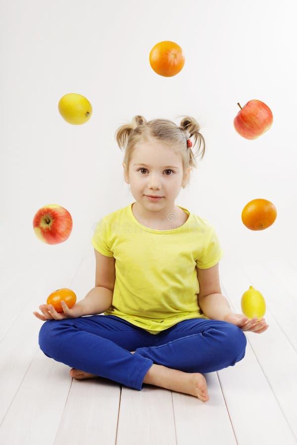 Meisje het jongleren met met vruchten stock foto