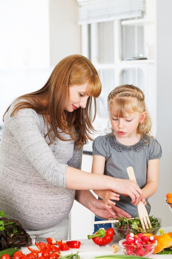Meisje het koken met haar moeder stock foto