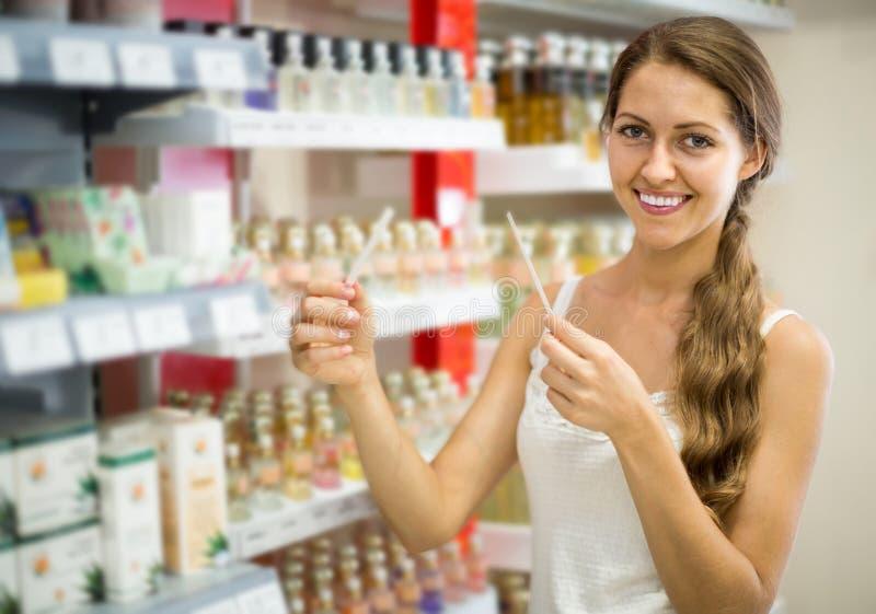 Meisje het kopen parfum in het winkelcomplex stock afbeeldingen