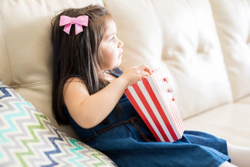 Meisje het letten op film in woonkamer royalty-vrije stock afbeelding