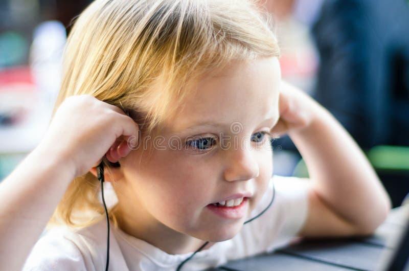 Meisje het letten op tablet of PC met oortelefoons Meisjeen stock afbeelding