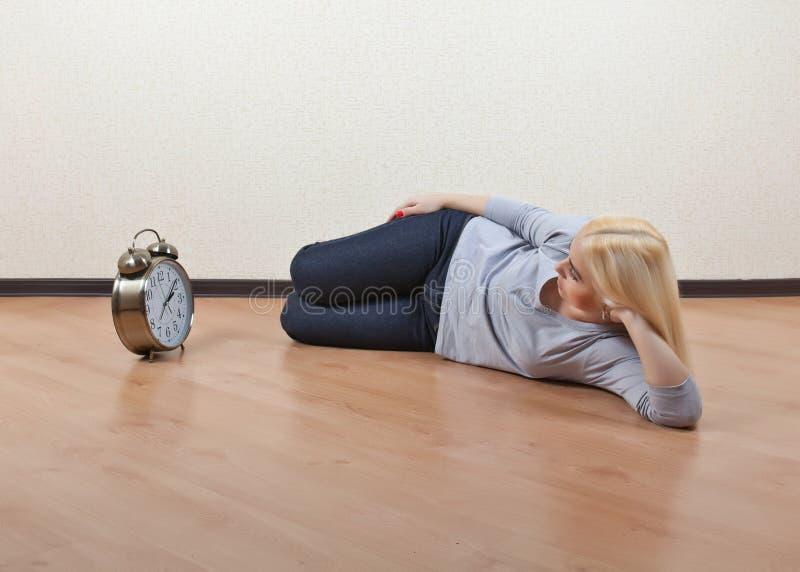 Meisje het liggen op de vloer en bekijkt zijn horloge stock foto