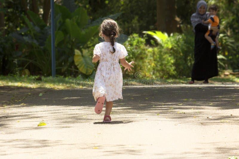 Meisje het lopen aan haar mamma en de broer op een vuil slepen in een park royalty-vrije stock afbeelding