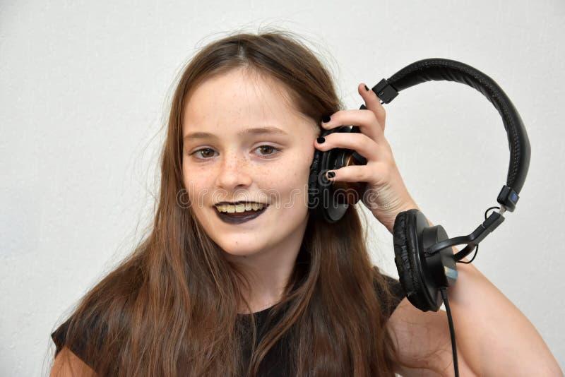 Meisje het luisteren muziek via hoofdtelefoons stock fotografie