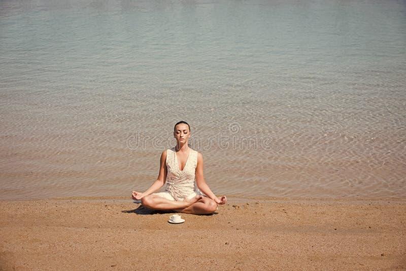 Meisje het mediteren in yoga stelt met koffiekop bij water royalty-vrije stock fotografie