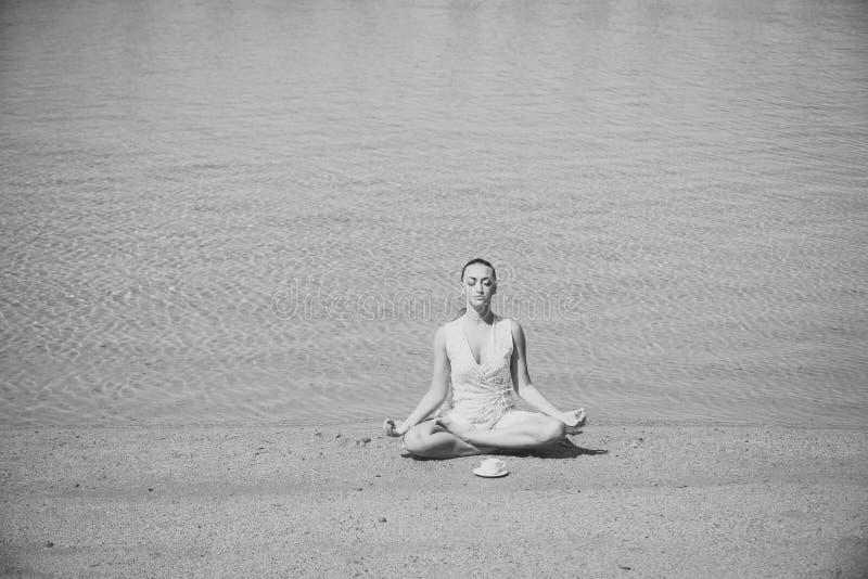 Meisje het mediteren in yoga stelt met koffiekop bij water stock fotografie