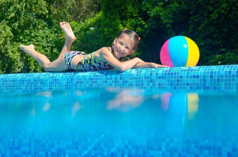 Meisje het ontspannen dichtbij pool, onderwater en boven mening stock fotografie
