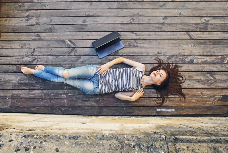 Meisje het ontspannen op een houten vloer Ontspan, rust, onderwijsconcept, recreatie stock fotografie
