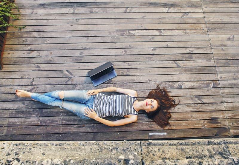 Meisje het ontspannen op een houten vloer Ontspan, rust, onderwijsconcept, recreatie royalty-vrije stock fotografie