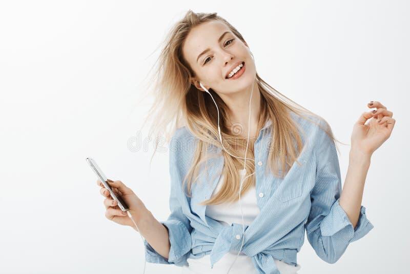 Meisje het ontspannen op manierhuis het luisteren favoriete liederen in oortelefoons Portret van gelukkige blije jonge vrouw met  royalty-vrije stock foto's