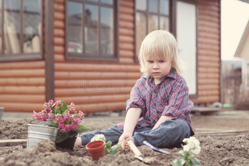 Meisje het planten en het water geven bloemen in tuin stock foto