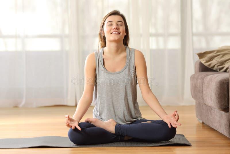 Meisje het praktizeren yoga op de vloer thuis royalty-vrije stock afbeelding