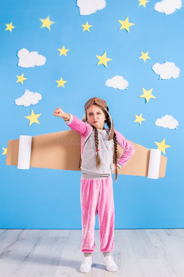 Meisje het proef spelen met stuk speelgoed straalpak thuis Succes en leidersconcept stock afbeeldingen