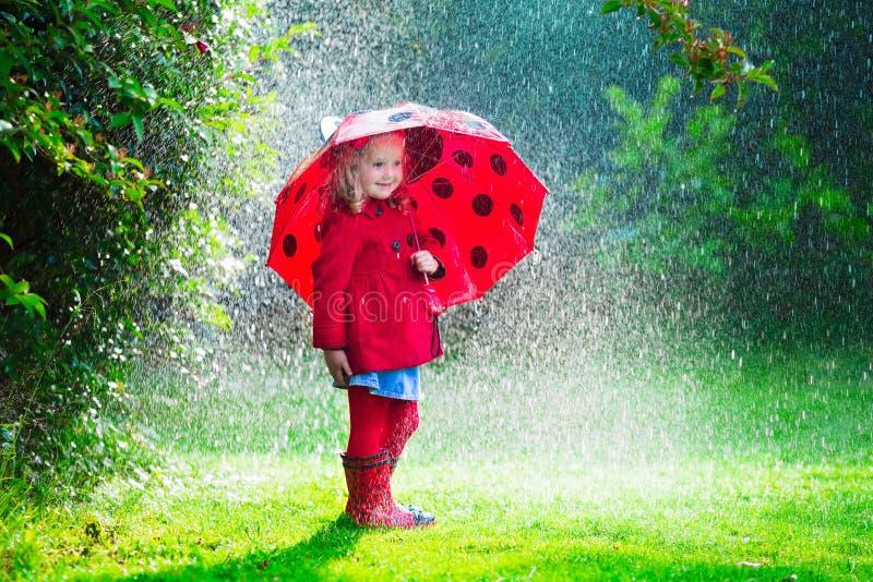 Meisje in het rode jasje spelen in de herfstregen royalty-vrije stock fotografie