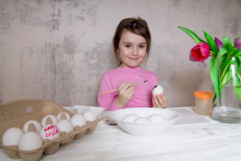 Meisje het schilderen eieren die voor Pasen voorbereidingen treffen stock afbeelding