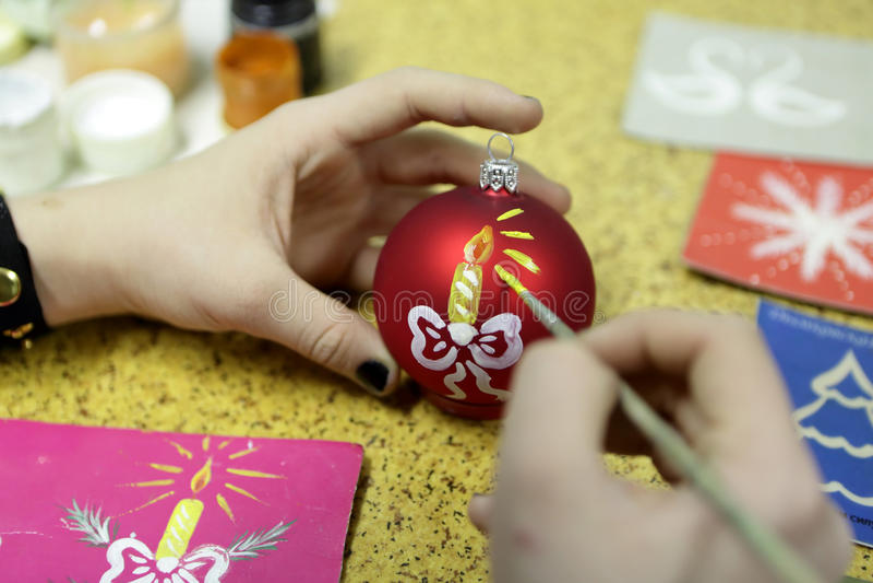 Meisje het schilderen Kerstmisbal stock foto