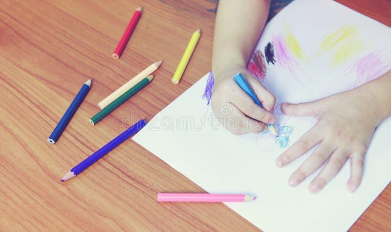 Meisje het schilderen op document blad met kleurenpotloden op de houten lijst thuis - kindjong geitje die tekeningsbeeld en kleur royalty-vrije stock afbeelding