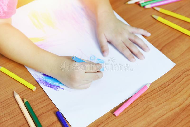 Meisje het schilderen op document blad met kleurenpotloden op de houten lijst thuis - kindjong geitje die tekeningsbeeld en kleur stock afbeeldingen