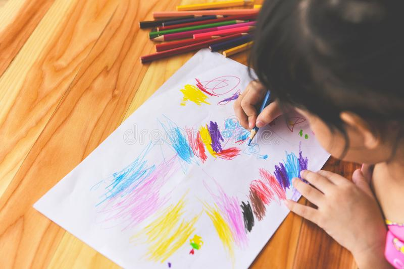 Meisje het schilderen op document blad met kleurenpotloden op de houten lijst thuis - kindjong geitje die tekeningsbeeld en kleur royalty-vrije stock foto